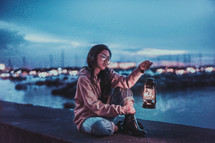 a woman sitting on a concrete wall holding a lantern by a marina