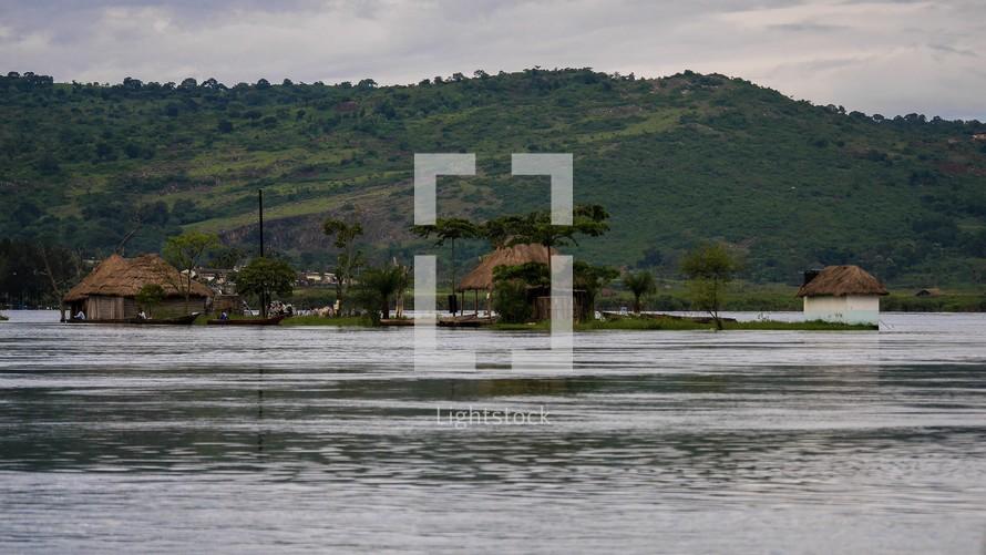 homes along a river in Uganda