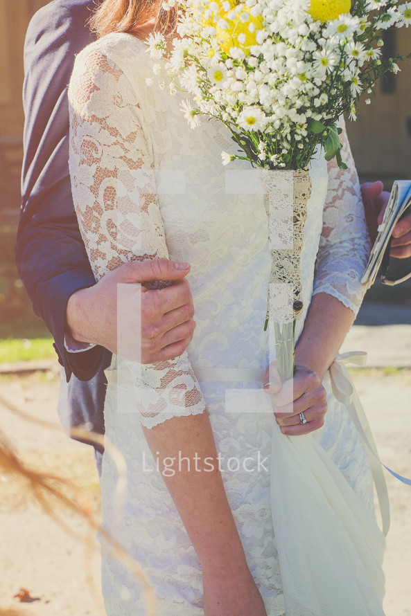 torso of a bride and groom snuggling