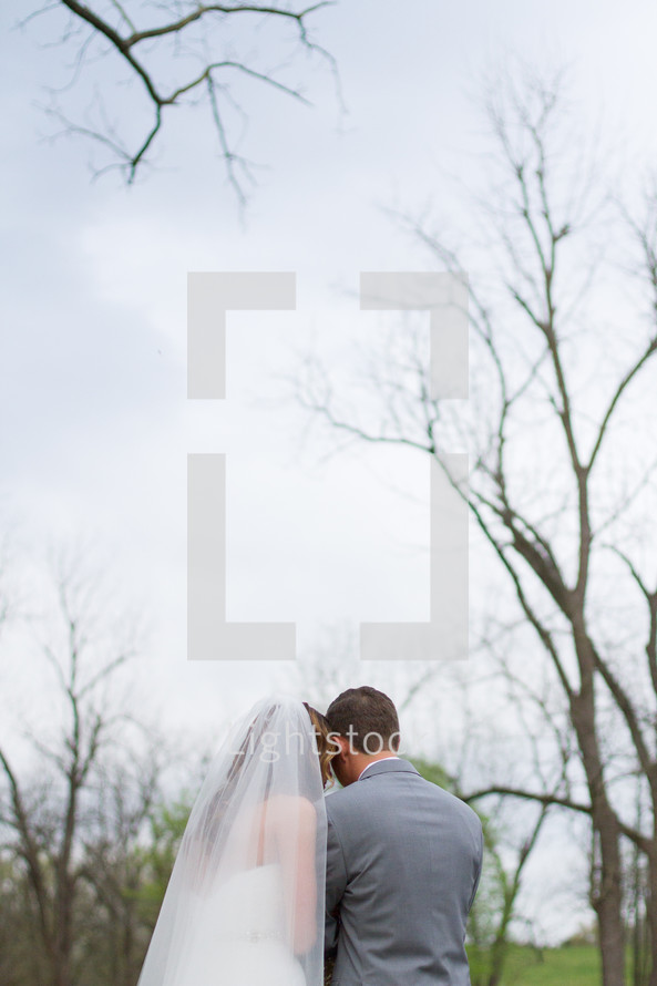 backs of bride and groom standing outdoors