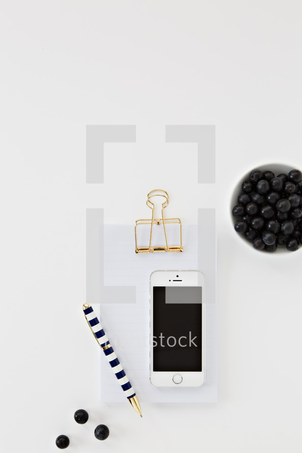 iPhone, clipboard, blueberries, and pen