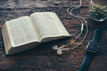 earbuds, open Bible, smartwatch, and houseplant on a wood background