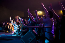 A group of young people lifting their hands in worship