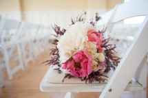 bridal bouquet on a white folding chair