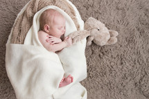 newborn holding a stuffed animal