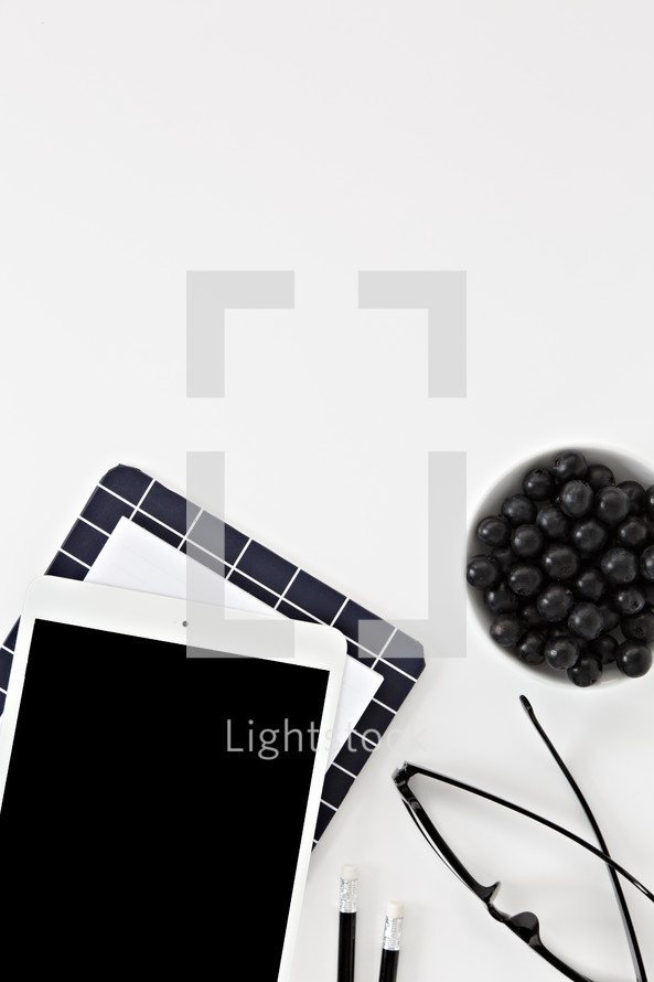 reading glasses, iPad, blueberries, and pencils