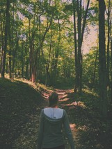woman walking on a path through a forest