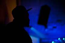 silhouette of a man in a hat at a concert
