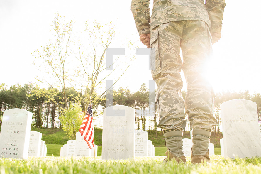 soldier standing in front of a cemetery