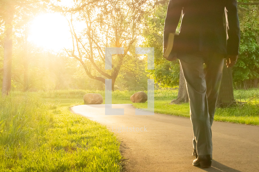 man carrying a Bible walking on a glowing path