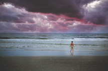 a boy standing on a beach under purple clouds in the sky