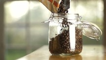 pouring coffee beans into a jar