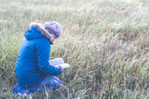 a woman kneeling in a field reading a Bible