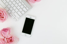 keyboard, pink roses, and cellphone on a white desk