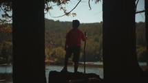 a boy with a walking stick looking out at a lake