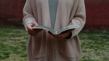 close up of a women opening a Bible.
