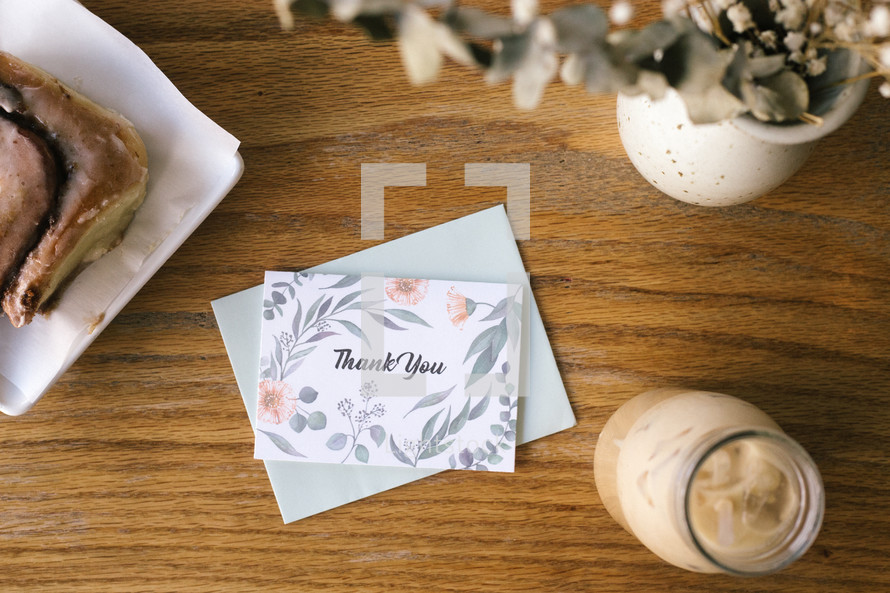 a thank you card on a wood table