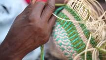 a woman weaving a basket