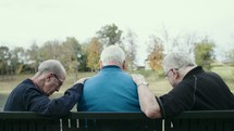 elderly men praying together sitting on a park bench