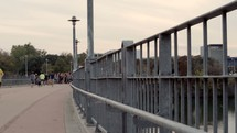 a woman looking over a railing of a bridge in a city