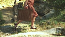 a woman walking up a mountainside carrying luggage