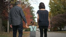 grandmother, grandfather, and granddaughter walking holding hands