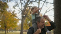 grandfather with his granddaughter on his shoulders