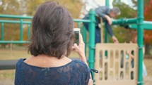 grandmother filming her husband and granddaughter on a playground