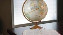 globe and opened Bible