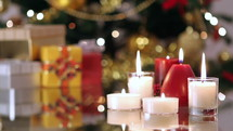 gifts and candles under a Christmas tree