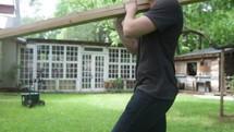 man carrying lumber