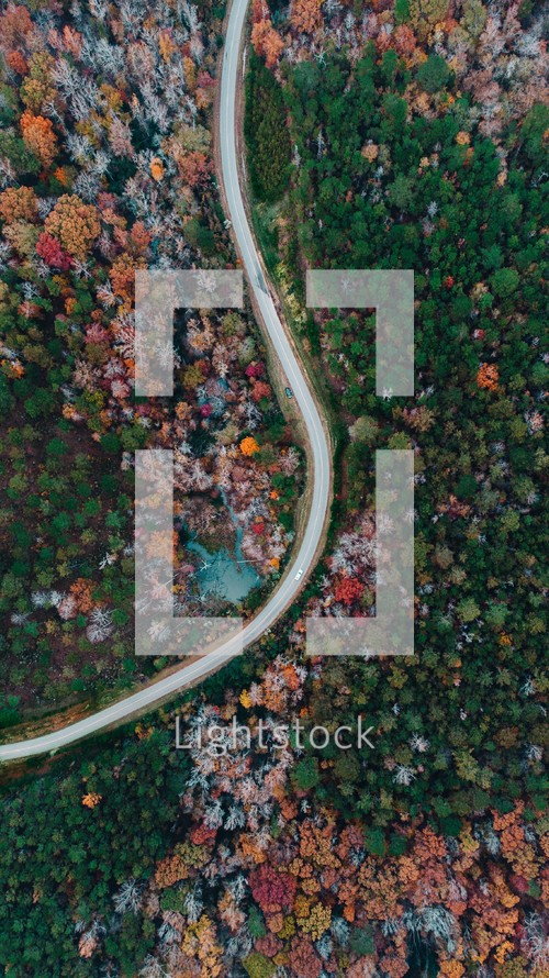 aerial view over a highway through a fall forest