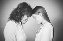 grandmother and granddaughter with heads bowed in prayer