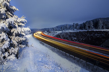 Light trails from a train running through a snow covered countryside.