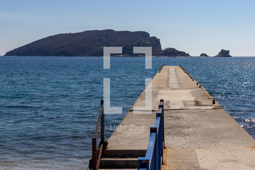Empty pier on Beach Greco with a view of Saint Nikola Island in the background in Budva, Montenegro