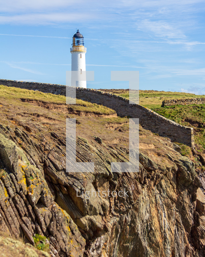 Rock wall leading to the Mull of Galloway lighthouse in Dumfries and Galloway, Scotland, United Kingdom under a blue sky with white clouds