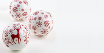 Three red and white Christmas balls on a white background.