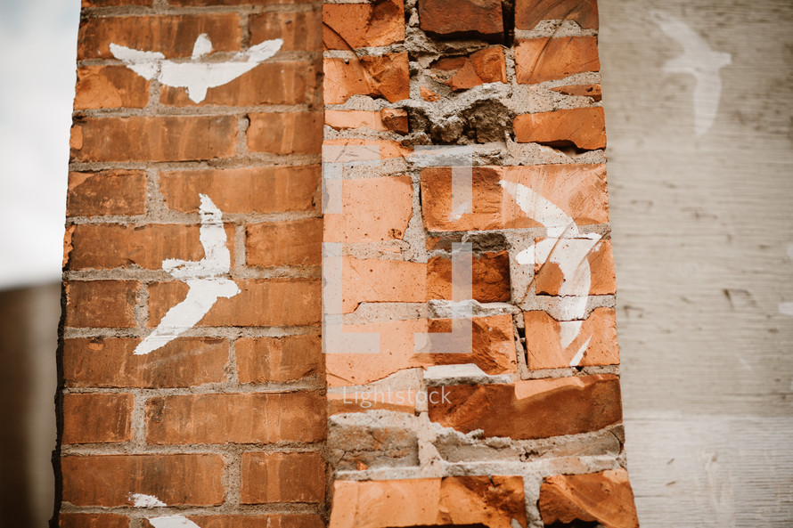 doves painted on a brick wall