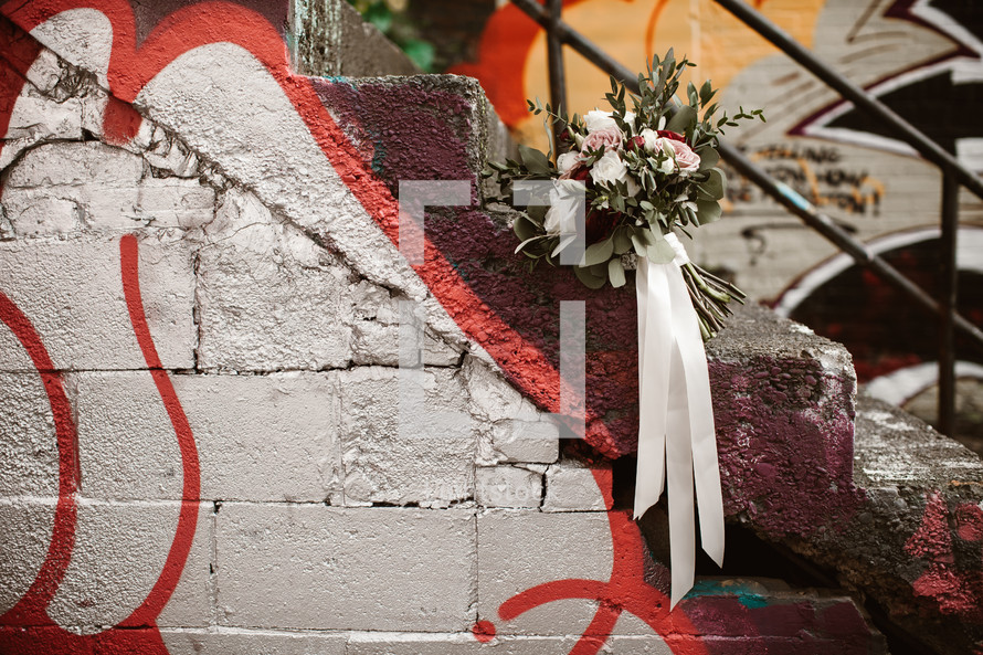 bridal bouquet on graffiti covered steps