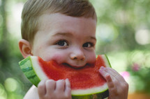 toddler eating a slice of watermelon