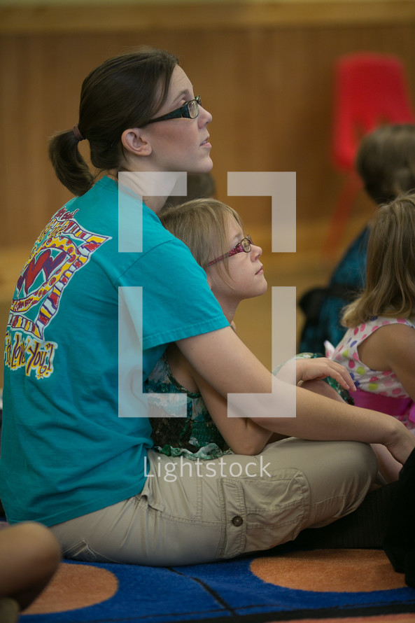 child sitting in her mother's lap during a children's ministry