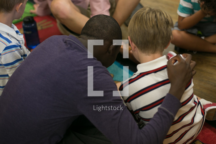 man with his arm around a child during a children's ministry