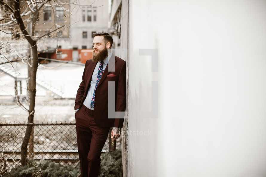 man in a suit leaning against a building