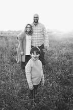 family portrait in a field of tall grasses