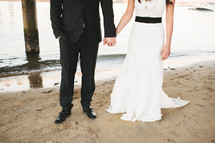 Bride and groom holding hands on beach.