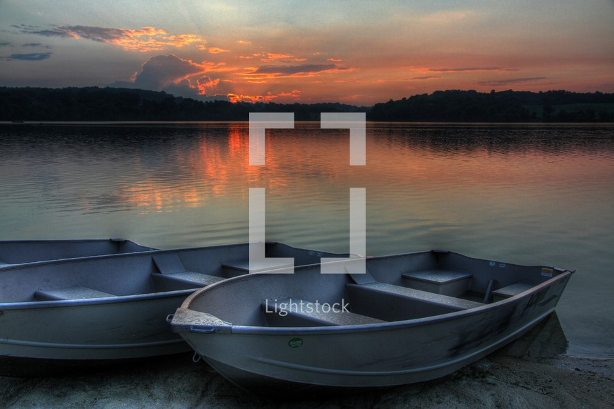 boat resting on the shore of a lake at sunset