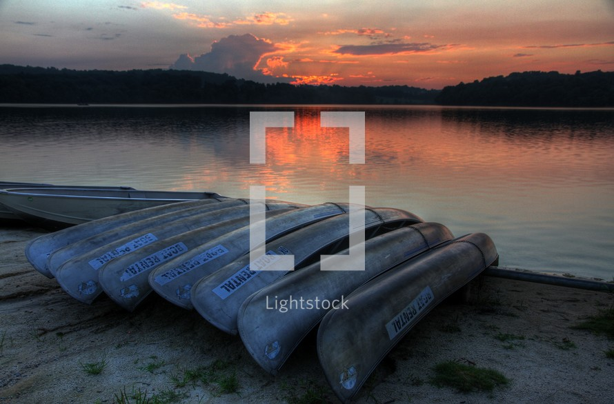 rental canoes flipped over on a lake shore at sunset