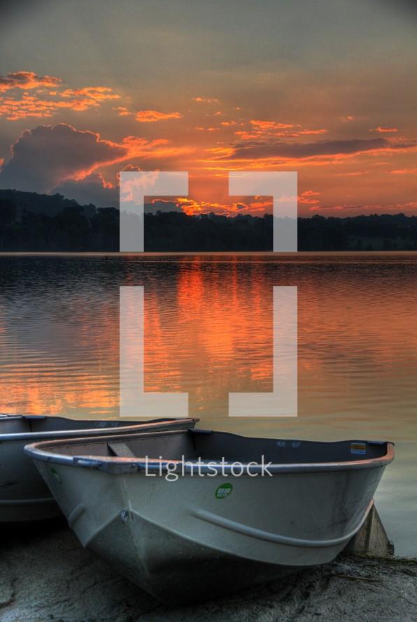 rental boats on a lake shore at sunset