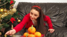 a child using a tablet on the couch next to a Christmas tree