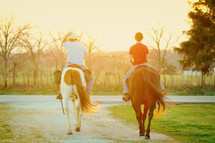 Two people riding horses.